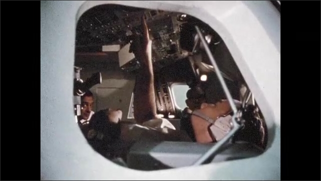 1960s: Two men sit at table together talking. Men in NASA mission control room talking. Men sit in cockpit of spacecraft. Man approaches radar dish building. Flying over boat in water.