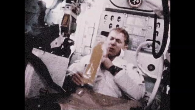1960s: Astronaut in spacecraft floats bag of food to other astronaut while weightless. Astronaut sucks food from bag. Woman packing space food. Man at chemistry station.