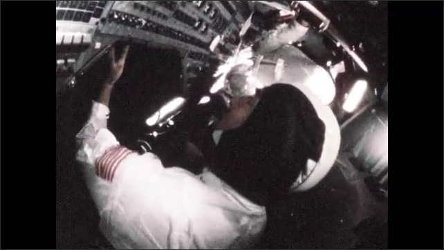 1960s: Person writes on health monitor readout. Man at mission control console. Astronauts in cockpit of spacecraft. Astronauts being assisted into spacecraft.