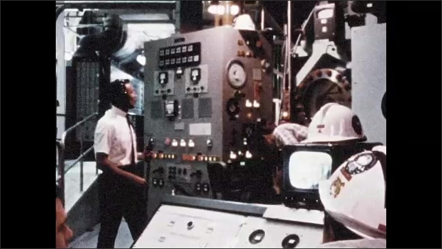 1960s: Interior of NASA facility. View through window, astronaut in space suit. Men with equipment. Astronaut in space suit. Equipment lowered in facility.