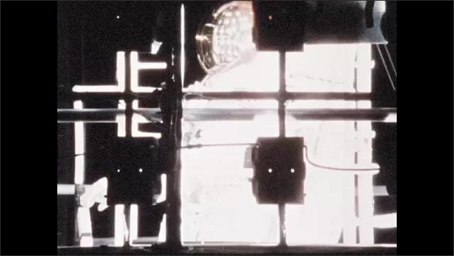 1960s: Astronaut climbing in chamber. Lights shine on astronaut in chamber. Men at control panel. Zoom out, astronaut in chamber. Exterior of facility.