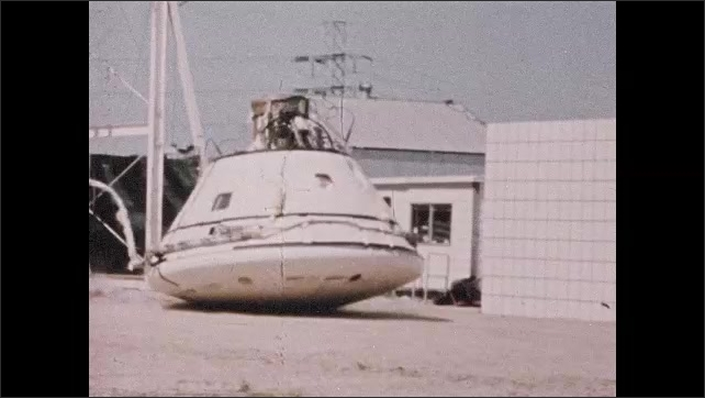 1960s: Man closes door to tank. Slow motion, space capsule dropped on ground.