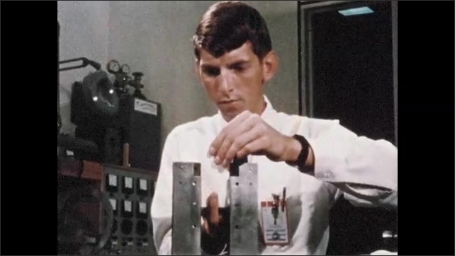 1960s: Man in lab, equipment moves. Close up, flame on piece of metal. Man puts object in clamp. Close up, material in clamp igniting.
