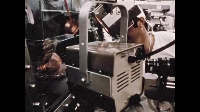 1960s: Exterior of NASA facility. View through tube, equipment moving. Men working in lab. Men in lab, pan to rock in machine. Close up of rock. Man looks in microscope. Magnified view of rock.