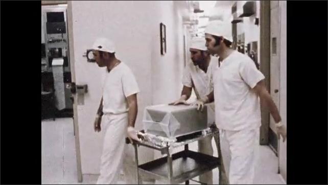 1960s: Tilt down scientific equipment. Men push cart through door. Low angle, man in lab. Equipment moving in lab.