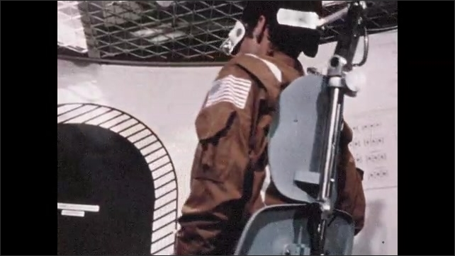 1960s: Man straps man into machine. Man presses button pan to man in chair, Man spinning in chair. Men inside spacecraft, Close up of controls.