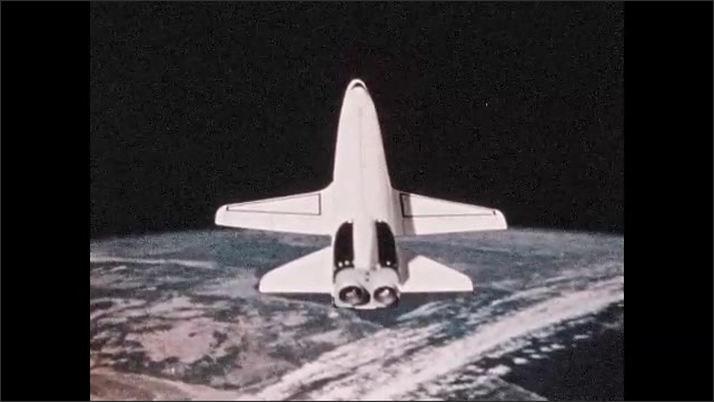 1960s: Space shuttle traveling over Earth. Rear view of shuttle flying.
