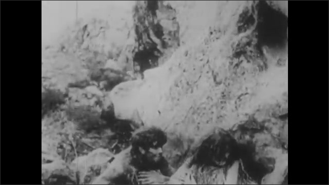 1910s: Man crawls to woman on ground, men crawl out from caves and scare away man.
