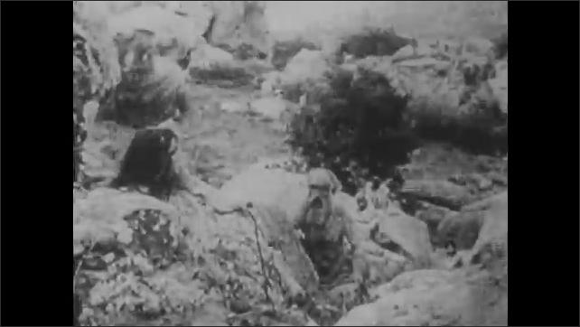1910s: People on rocks, man walks down hill. Man and woman on hill, woman runs away.