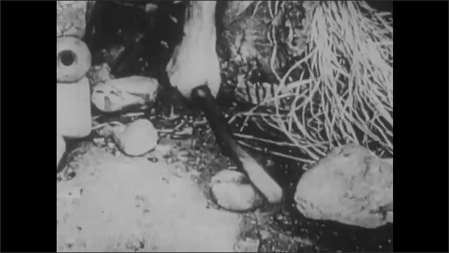 1910s: Man sitting in cave, picks up stick. Hand hits at rock with stick, rock slides onto stick.
