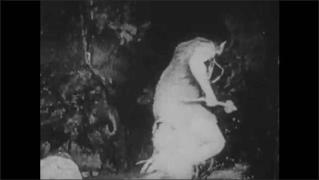 1910s: Woman sitting by rock. Man in cave stands, exits. Man climbs out of cave, runs with club.