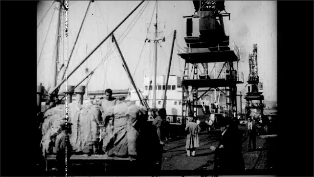 1960s: men looking for work at dock, dock workers using cranes to load cargo onto boats