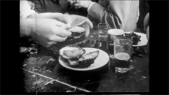 1960s: people crowding restaurant and bar eating oysters and other foods