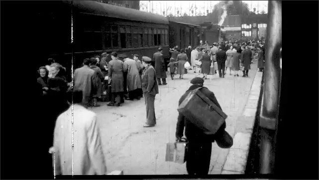 1960s: train station as train comes into station, people getting luggage together to board train