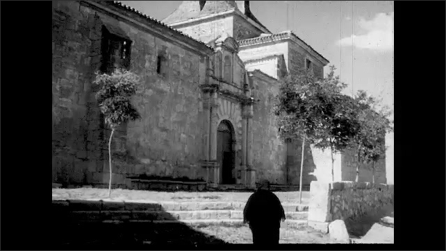 1960s: Spanish village in countryside, church, priests leading two boys into church