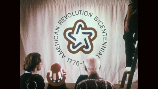 1970s: People gather in front of banner, zoom in to logo on banner.