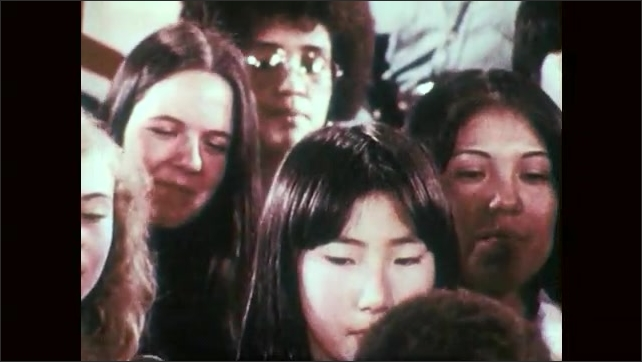1970s: Hand lights candle on cake, zoom out to people singing, pan across cake. Tracking shot of people singing. Tracking shot of cake.