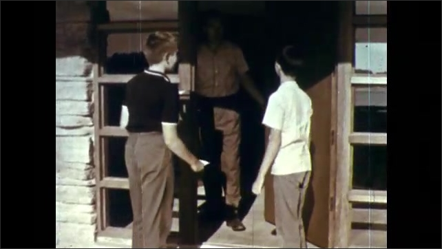 1950s: Small sign above doorbell. Finger pushes doorbell. Boys stand at front door of home. Man answers front door and speaks to boys. Boy smiles and responds.