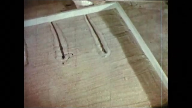 1950s: Boy slides yard stick across table and draws lines in sand. Man removes scale model homes from shelf and hands them to boy.