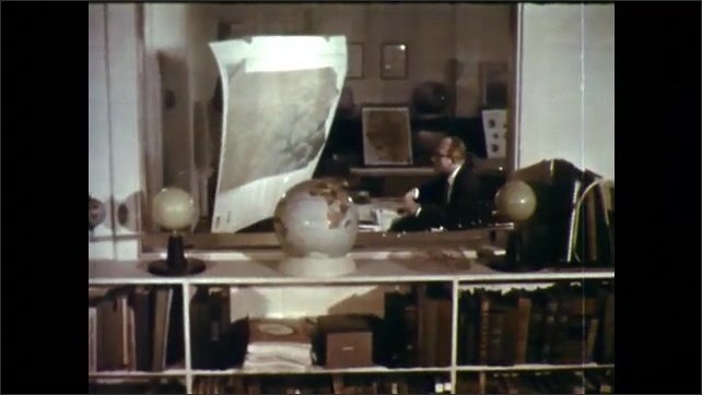 1950s: Man tapes down acetate map onto table. Man carries large map of Pennsylvania into office. Men observe map at desk. Boys point to scale model of neighborhood with stick.