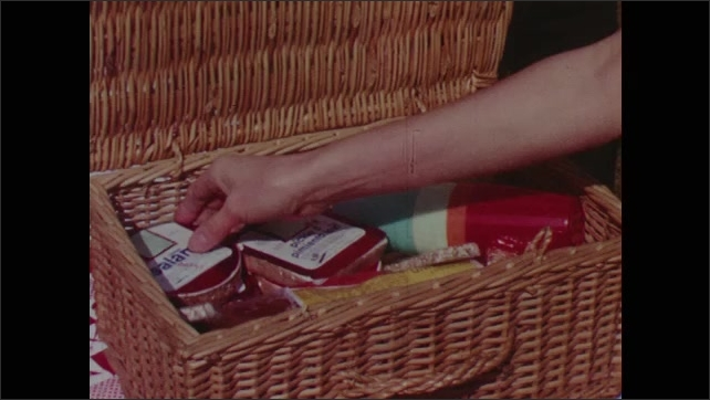 1960s: Picnic blanket with a radio and basket on it. Woman unpacks the picnic basket, including a package of salami.