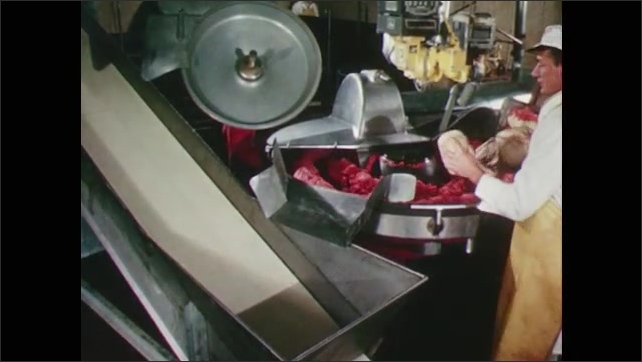 1960s:USDA meat inspector looks at meat about to be put through grinder. Meat processing plant worker pours spices and salt on meat in the grinder.