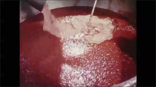 1960s:USDA meat inspector looks at meat and other ingredients added to a commercial vat of spaghetti sauce. Inspector looks with a skeptical face at the vat.