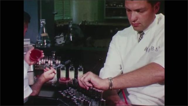 1960s: Lab technician studies colored liquid in beakers. Technician works on sample in a petri dish.