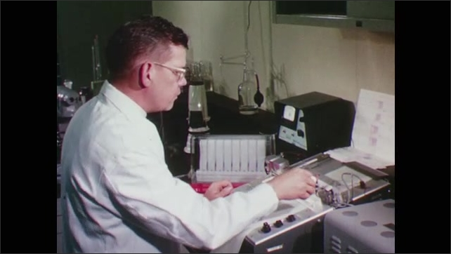 1960s: Scientist adjusts paper and recording machinery in a laboratory.