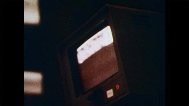 1970s: Men watch. Lander I and parachutes drive toward surface of Mars. TV screen displays image of Mars' surface.
