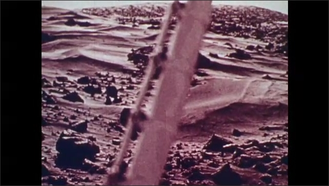 1970s: Bottles on conveyor move. Needle on gauge moves from left to right. View of surface of Mars.