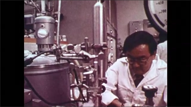 1970s: Men in control room. Researcher works in lab. Tubes spin in centrifuge.