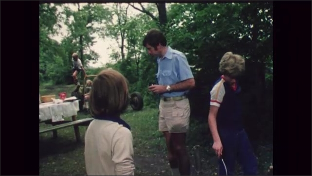 1980s: UNITED STATES: sausages cook in pan. Boys at summer camp in forest. Boys cook breakfast.