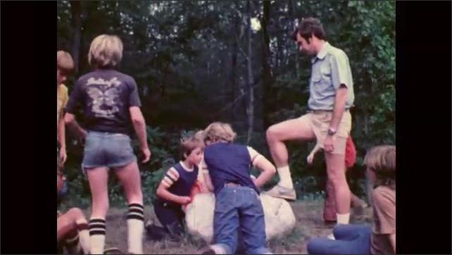 1980s: UNITED STATES: boys play Frisbee at camp. Boys enjoy summer camp in woods. Boys sit around rock. Man talks to boys.