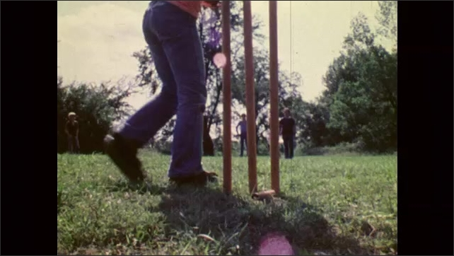 1980s: UNITED STATES: boys play cricket at summer camp. Hands prepare to catch ball. View of wickets in game of cricket.