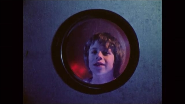 1980s: Face of a boy who looks out from a circular window, a red light blinks behind him. Outer space and stars. Boy with admiring look. Model of the Moon's surface, lunar craters, moon mountains.