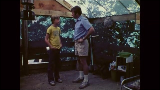 1980s: Man washes his hands inside a hut, dries his hands and talks to a boy, the boy talks. Two boys lay in bed at night, one boy reads and the other boy talks, two boys talk in bed.