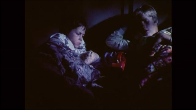 1980s: Face of boy who lays in bed at night. Two boys lay in bed, a boy closes the book, switches off the lamp, they lean back and cover themselves, they talk and fall sleep.