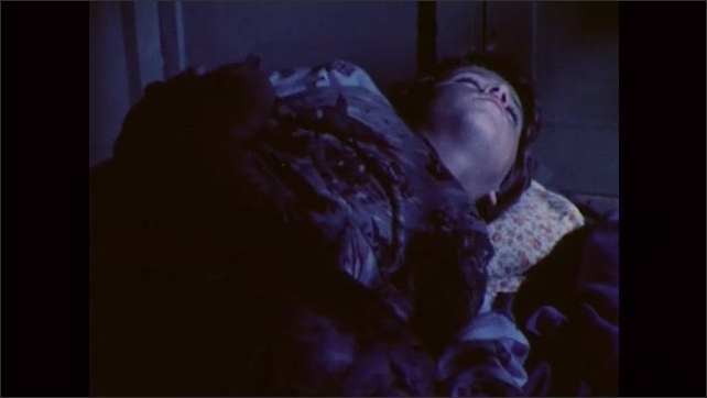 1980s: Smoke comes out from a campfire. A boat in a lake at dawn. Face of a boy who sleeps, another boy lays next to him and moves in his sleep, he wakes up, sits in bed and looks outside.