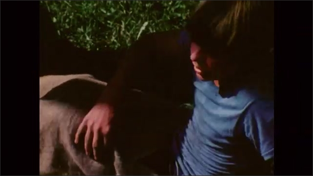 1980s: Man watches boys who play sack race, some boys fall on the ground. A boy sits on the ground with a sack on his legs and talks, boys lay on the grass and talk.