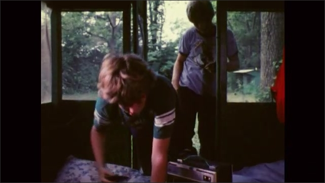 1980s: UNITED STATES: smoke above camp fire. Boys run to cabin. Boys play cassette.