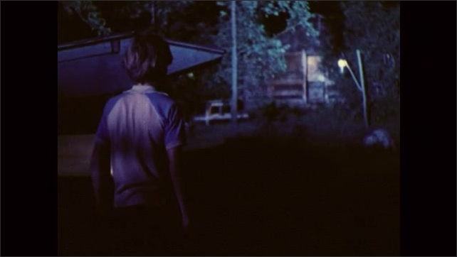 1980s: UNITED STATES: boy outside cabin at night. Boy whistles