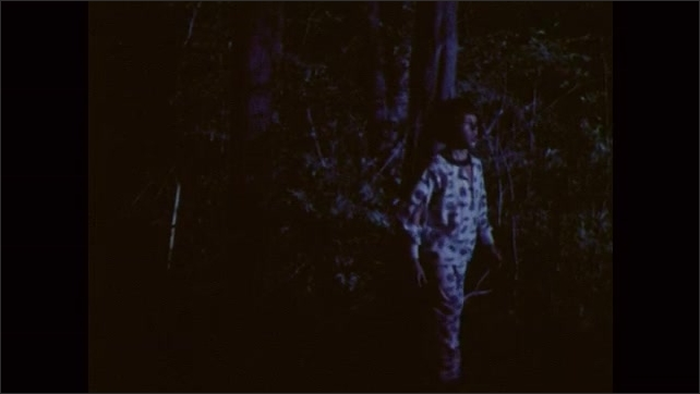 1980s: UNITED STATES: boy in pajamas walks through woods at night. Boy gives cassette player to man. Man holds up cassette player