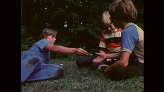 1980s: UNITED STATES: boys play cricket at summer camp. Boy shares chewing gum. Boys eat gum