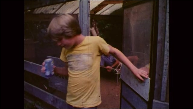 1980s: UNITED STATES: man talks with boy at camp headquarters. Boy drinks can of soda. Boy sleeps in bed at night. Camp fire at night