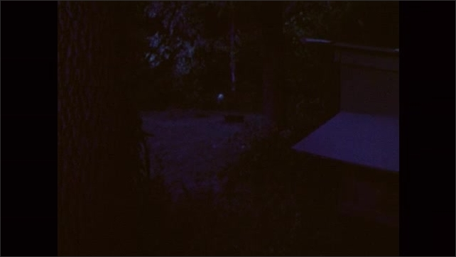 1980s: UNITED STATES: boy walks in woods at night. Man talks to boy by cabin.