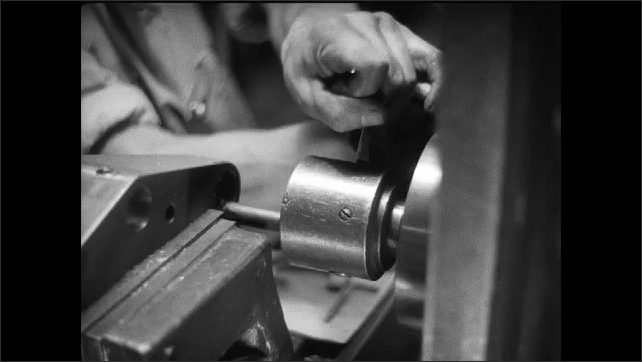 1930s: Man operates machinery, watches metal cylinder spin.