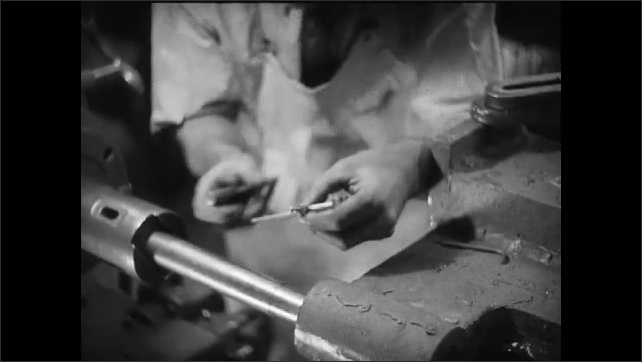 1930s: Man looks through eyepiece on machine. Man measures and adjusts machinery. Man looks down.