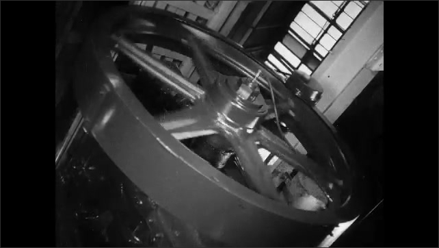 1930s: Man turns wheel. Needle on large dials hovers in place. Man lifts lever, wheel spins. Man operates machinery, wheel spins.