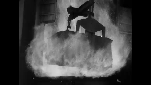 1930s: Large bin is lifted up. Fire burns, man adjusts knobs. Large bin is moved into fire and pulled out of fire.
